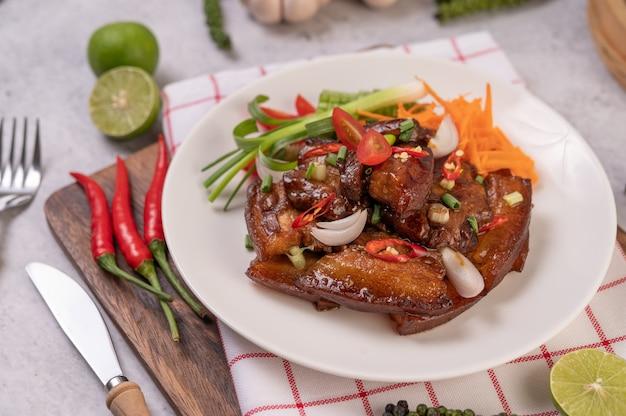 Dulce de cerdo en un plato blanco con cebolletas picadas, ají, lima, calabaza, tomate y ajo.