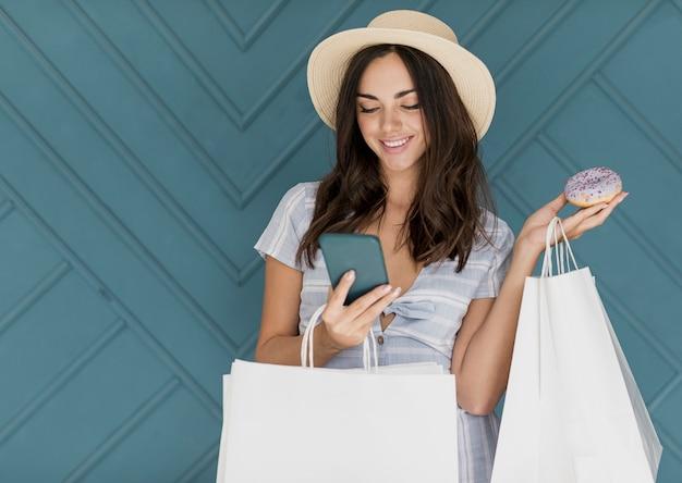 Dulce dama con sombrero mirando smartphone
