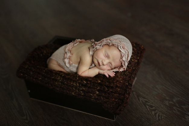 Dulce durmiendo perezoso bebé en caja, estilo oscuro
