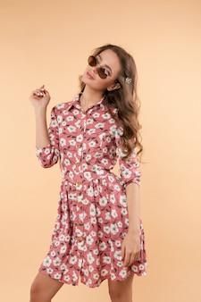 Dulce y encantadora chica en bonito vestido de verano con bolso y gafas de sol.