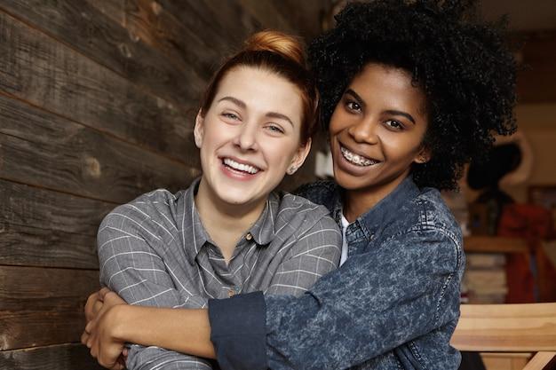 Dulce foto de la feliz pareja femenina del mismo sexo abrazados, riendo alegremente mientras pasan un buen rato juntos en el café