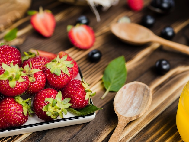Dulce fresas frescas y cucharas sobre fondo de madera