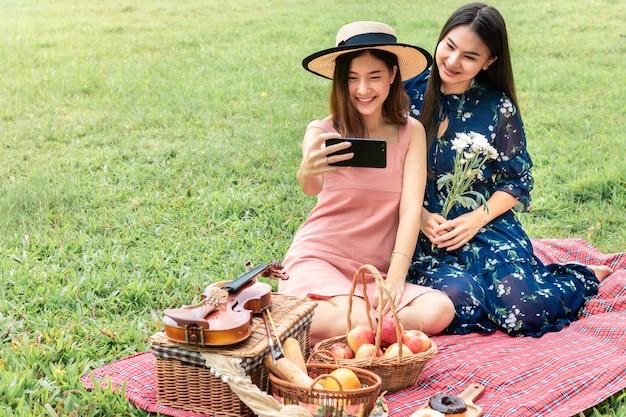 Dulce momento de amor. retrato de pareja homosexual asiática divertida selfie y picnic en el parque. concepto lgbt leasbian.