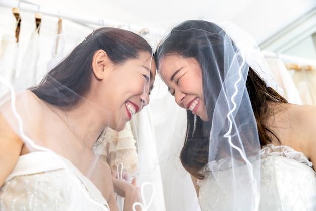 Dulce momento de amor. retrato de pareja de homosexuales asiáticos en vestido de novia. concepto de lesbiana lgbt.