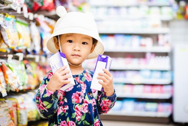 Dulce niña asiática comprando en mini mart con cesta, disfruta comprando algo en mart