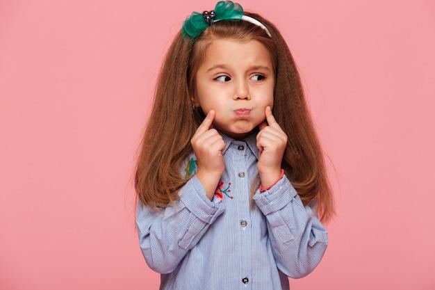 Dulce niña caucásica con hermoso cabello castaño largo explotando sus mejillas tocando la cara
