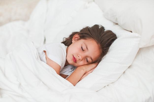 Dulce niña, durmiendo tranquilamente en su cama con las manos debajo de la cabeza