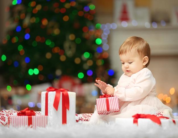 Dulce niña jugando con regalos en navidad