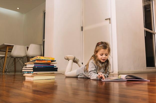 Dulce niña leyendo libros en el piso