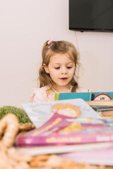 Dulce niña leyendo en la mesa