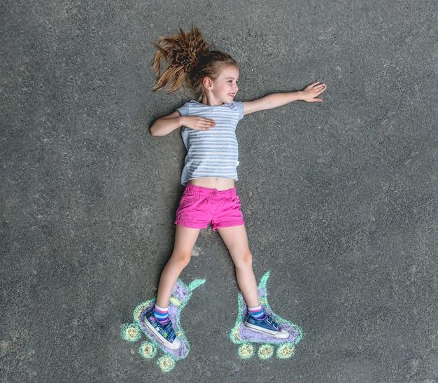 Dulce niña en patines pintados con tiza