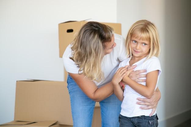 Dulce niña de pelo rubio y su madre mudándose a un nuevo piso, de pie cerca de la pila de cajas y abrazándose