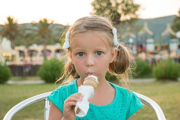 Dulce niña rubia en camiseta verde comiendo su helado