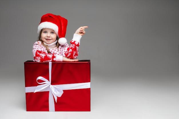 Dulce niña en suéter de invierno estampado y gorro de papá noel que indica en el espacio en blanco apoyándose en envuelto regalo de navidad con lazo blanco.