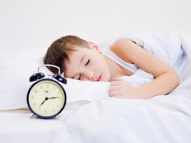 Dulce niño durmiendo con despertador cerca de su cabeza