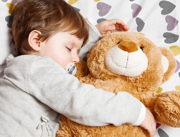 Dulce niño durmiendo con osito de peluche.