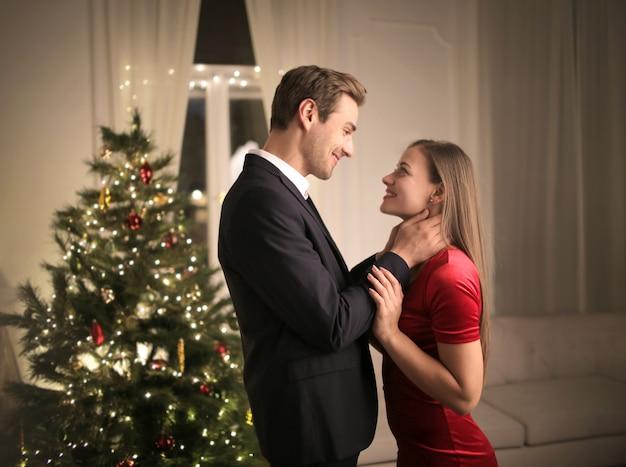 Dulce pareja abrazados en casa, celebrando la víspera de navidad