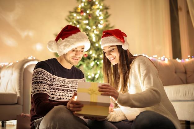 Dulce pareja abriendo regalos de navidad juntos