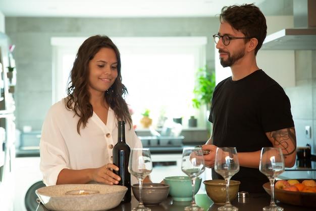 Dulce pareja cocinando y sirviendo vino