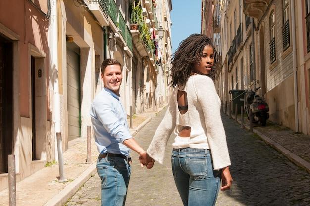 Dulce pareja interracial de pie para la cámara