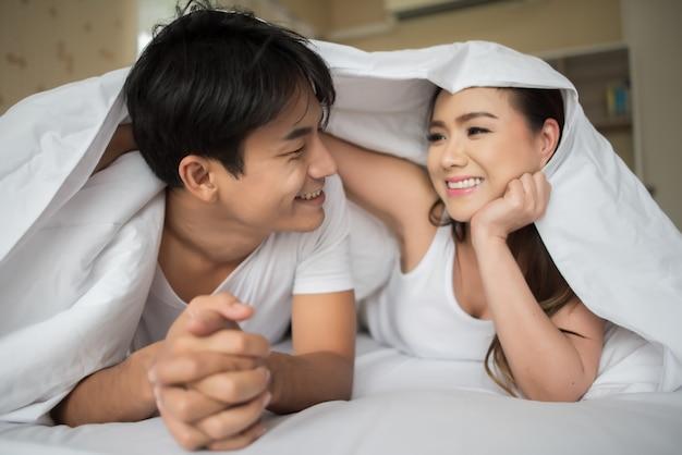 Dulce pareja jugando bajo la manta en la cama