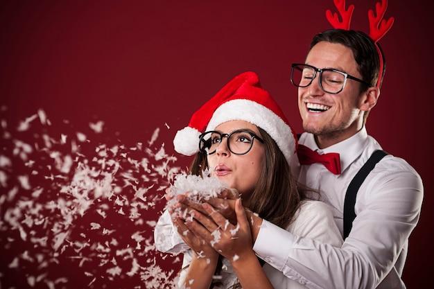 Dulce pareja nerd soplando nieve