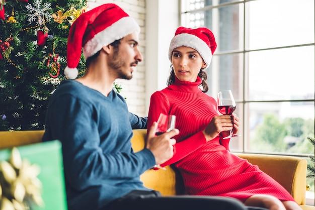 Dulce pareja romántica con sombreros de santa divirtiéndose y bebiendo copas de vino mientras celebran la víspera de año nuevo y disfrutan pasar tiempo juntos