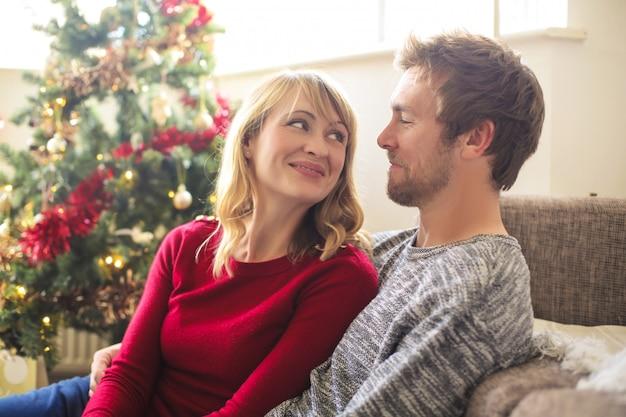 Dulce pareja sentada en la sala de estar, celebrando la navidad