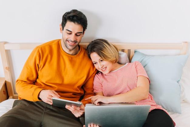 Dulce pareja usando tecnologías en la cama
