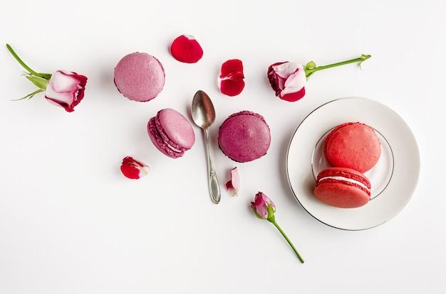Dulce postre francés y rosas sobre fondo blanco.