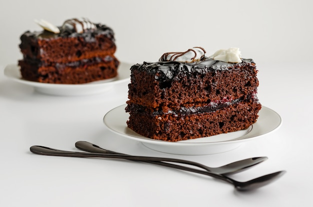 Dulce rebanada de pastel de chocolate sobre fondo blanco.