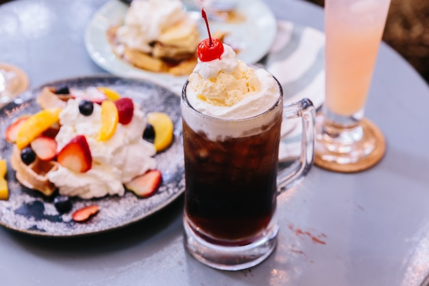 Dulce y refrescante cobertura de cherry cola con una bola de helado de vainilla y cereza fresca.
