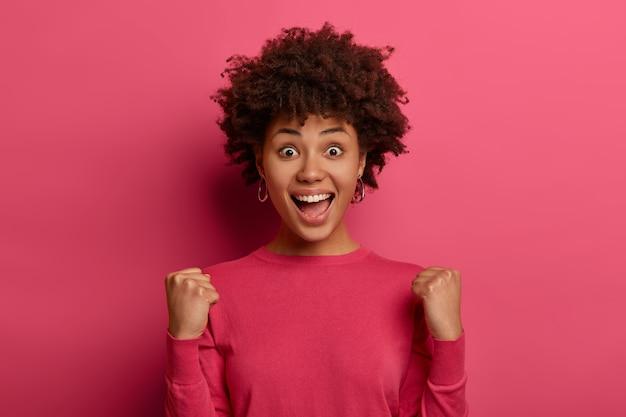 Dulce sabor del éxito. la mujer de piel oscura alegre y positiva levanta los puños cerrados, logra el éxito, exclama positivamente, grita que sí, aplaude la victoria, feliz de convertirse en campeona, aislada en la pared rosa