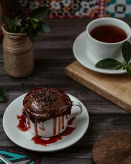Una dulce taza de mousse de chocolate sabroso con jarabe de fresa en el interior servido con una taza de té