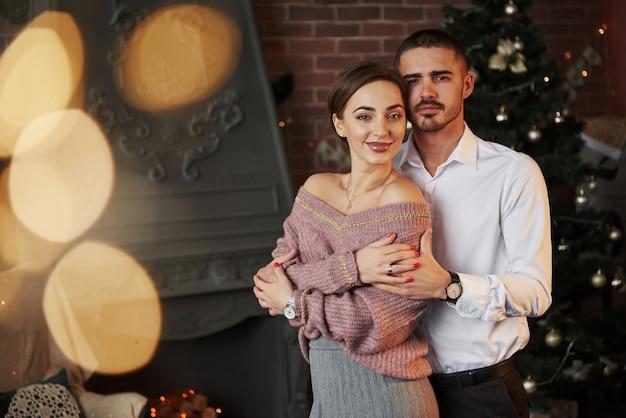 Dulces amantes elegantes. bonita pareja celebrando año nuevo delante del árbol de navidad