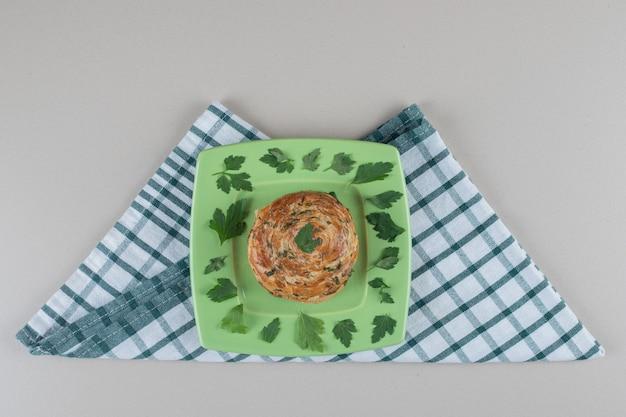 Dulces amargos en un plato decorado con hojas de perejil sobre una toalla doblada sobre fondo de mármol.