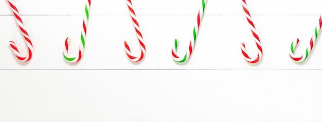 Dulces de bastón de caramelo de navidad en fondo de banner de madera blanco
