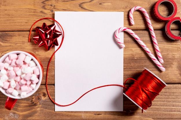 Dulces bastones de navidad y hoja en blanco