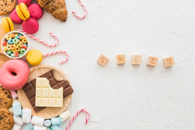 Dulces bloques cúbicos cerca de alimentos poco saludables en el fondo blanco