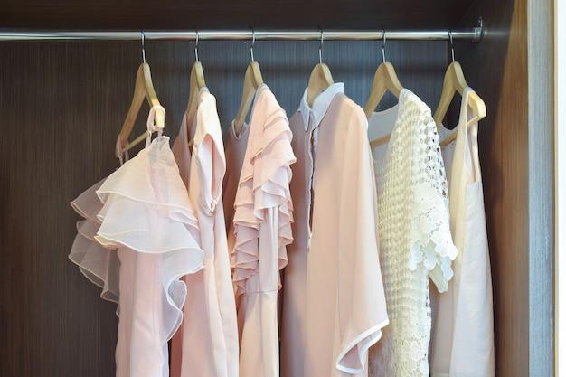 Dulces blusas en colores pastel están colgando en el armario de madera abierta