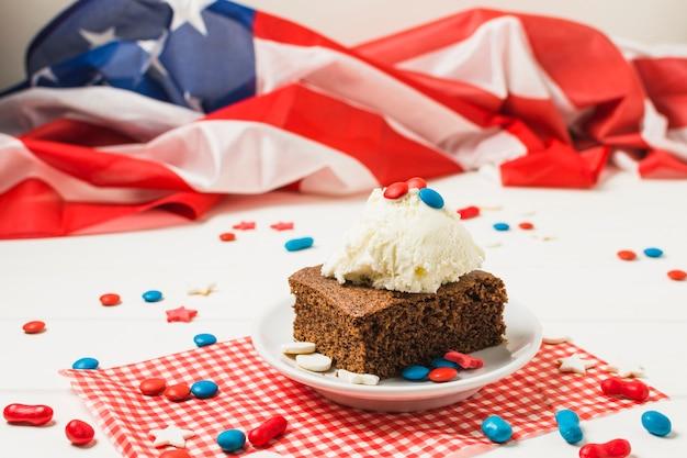 Dulces caramelos servidos con una cucharada de helado y pastel frente a la bandera de los ee. uu. en el escritorio blanco