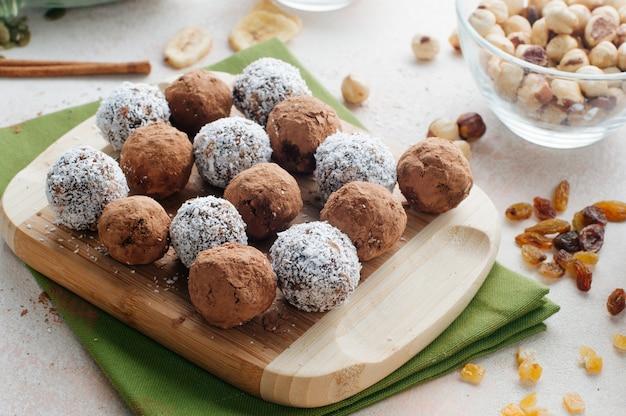 Dulces caseros veganos de frutas secas y nueces cubiertas con polvo de cacao y chips de coco