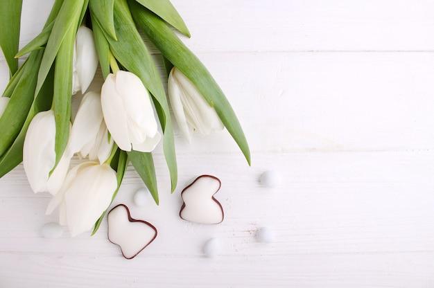 Dulces para celebrar la pascua. tulipanes blancos, huevos de chocolate y conejito de pascua.
