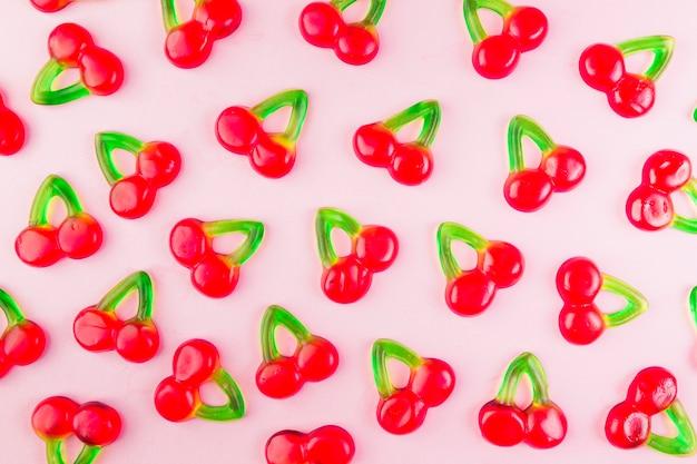 Dulces de cereza dulce gelatina en superficie rosa