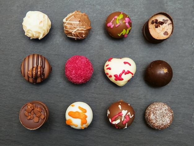 Dulces de chocolate de colores sobre un fondo de bandeja de pizarra gris