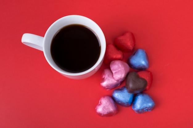 Dulces de chocolate en forma de corazón con café