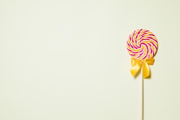 Dulces dulces de piruleta con espacio para texto sobre fondo de color amarillo, vista superior en plano