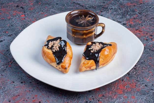 Dulces frescos con chocolate caliente en la placa blanca.