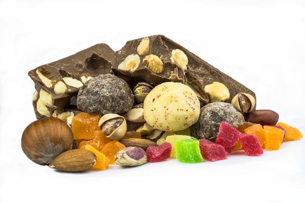 Dulces hechos de chocolate blanco y negro, frutas confitadas y chocolate, nueces aisladas sobre fondo blanco.