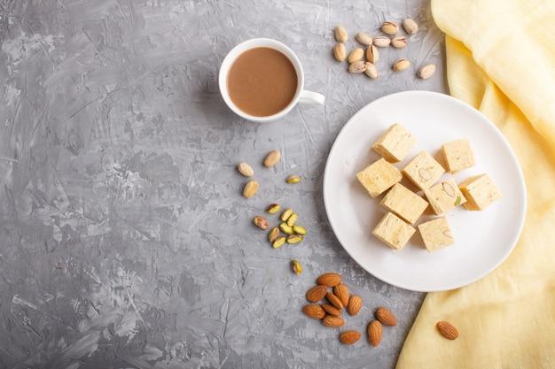 Dulces indios tradicionales papdi soan en plato blanco con almendras y pistachos sobre un hormigón gris.
